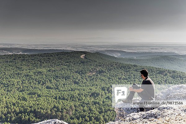 Man at top of hill looking panoramic views of Castile y Leon area from Canyon of Rio Lobos  Soria. Spain.