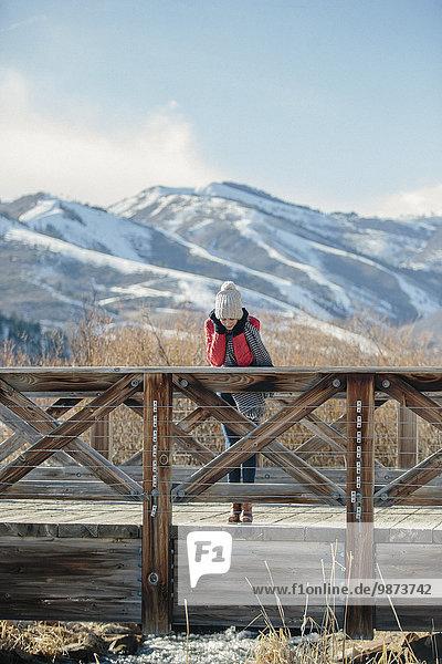 Fußgängerbrücke angelehnt Geländer über klein Hut Jacke rot Strickkleidung Mädchen