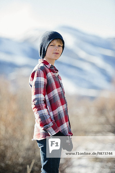 A boy with a woolly hat and checked shirt standing in open countryside in winter.