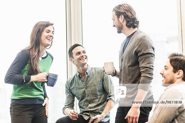 Vier Arbeitskollegen in der Pause  die zusammen lachen.
