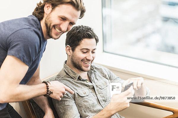 Ein Mann sitzt und schaut auf sein Smartphone und ein Kollege schaut ihm über die Schulter.