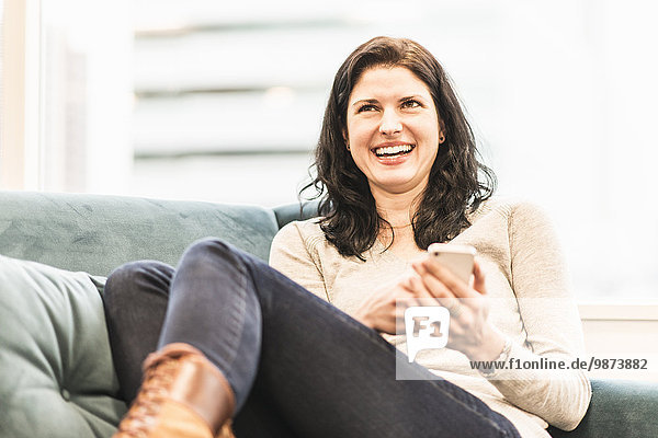 A woman seated with her feet up on a sofa  looking at her smart phone.