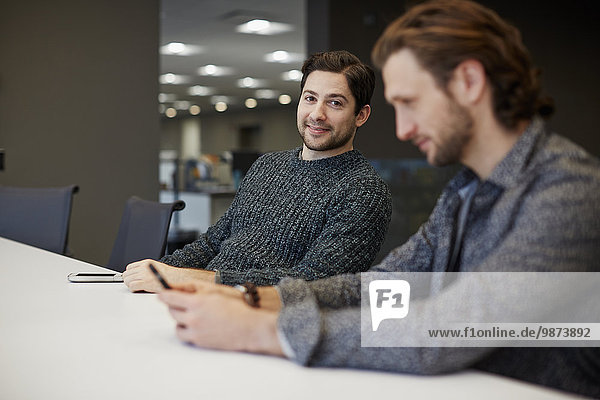 Two men seated at a table  one using his smart phone.