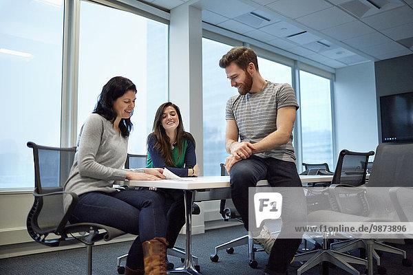 Drei Kollegen bei einer Besprechung  zwei Frauen und ein Mann am Rande des Tisches sitzend. Sie sehen sich Proofs von gedruckten Seiten und Entwürfen an. Eine kreative Umgebung.