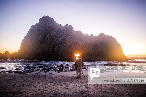Photographer photographing rock formation on beach  Big Sur  California  United States