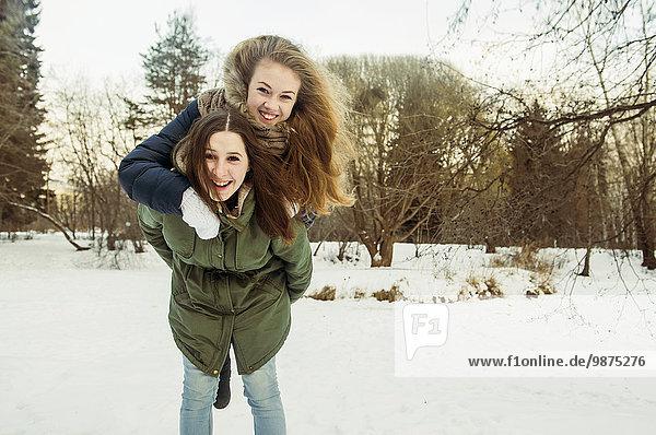 Europäer Frau tragen Schnee Feld huckepack Freund