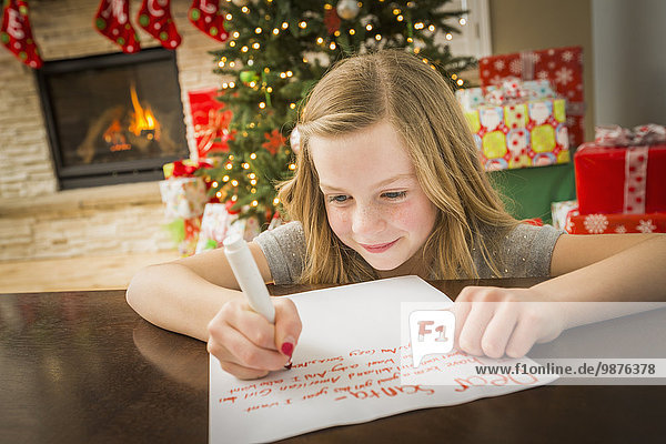 Caucasian girl writing to Santa at Christmas