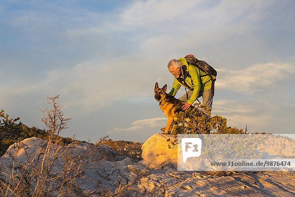 Older man and dog on remote rock formations