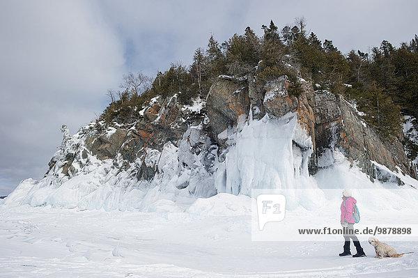 nahe Wasserrand Frau Winter Felsen Hund See Eis wandern gefroren