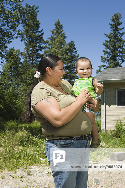 Native American Mother With Her Son Standing Outside In Front Of A Home.
