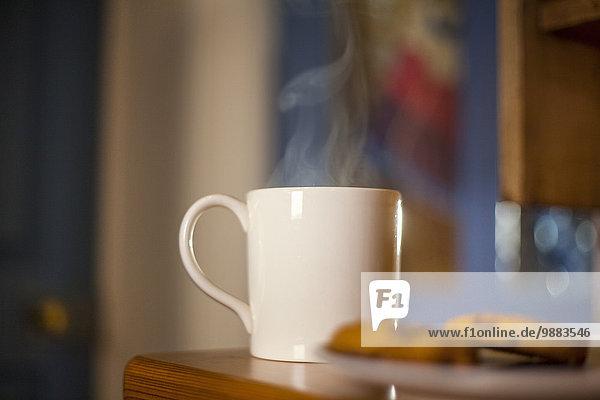 Tasse Kaffee und Kekse auf dem Tisch
