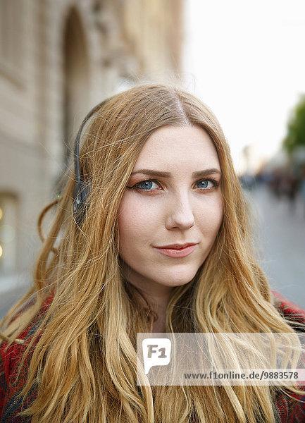 Portrait einer blonden jungen Frau mit Kopfhörer