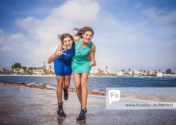 Porträt von zwei jungen Frauen  die auf der Promenade herumtollen.
