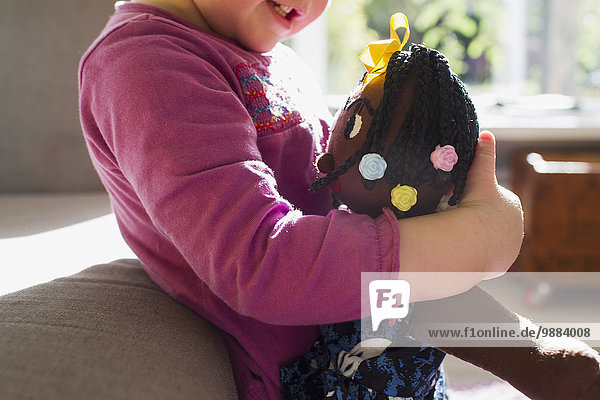 Cropped shot of baby girl in living room hugging rag doll