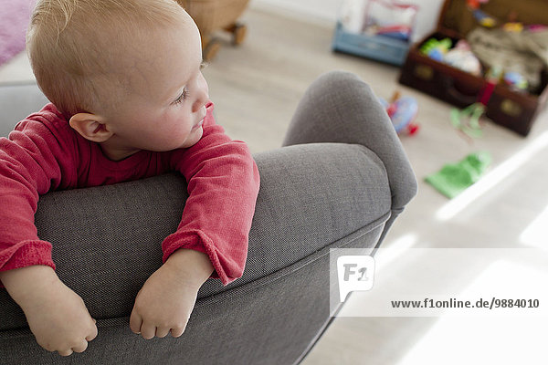 Baby girl in living room leaning on sofa