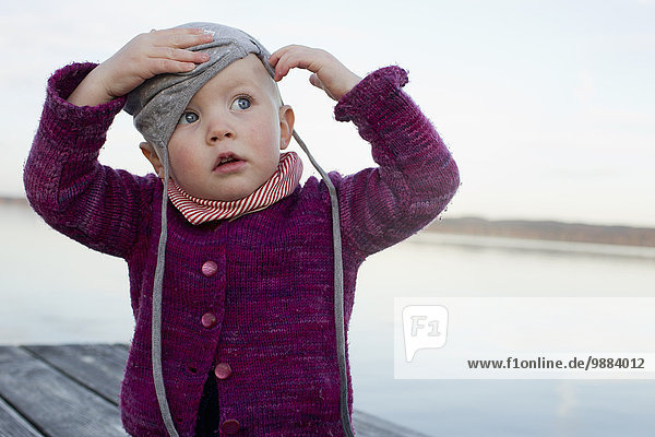 Baby girl on lake pier trying to put on hat