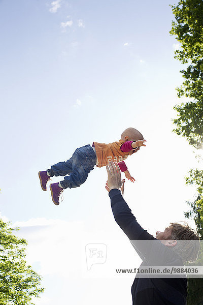 Father throwing baby daughter mid air in park