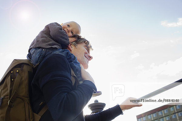 Father giving baby daughter shoulder ride in city