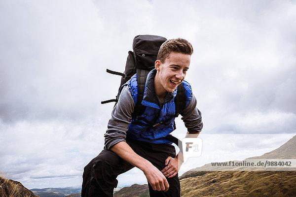 Junge männliche Wanderer  die den Gipfel des Berges erreichen  The Lake District  Cumbria  UK