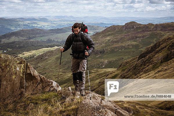 Junge männliche Wanderer  die sich auf den Berg bewegen  The Lake District  Cumbria  UK