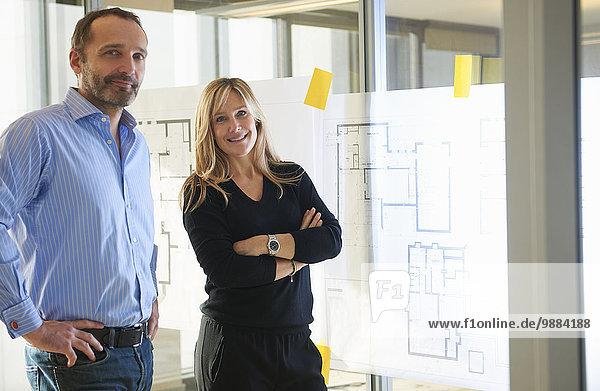 Architekten stehen nach Plänen an der Glaswand