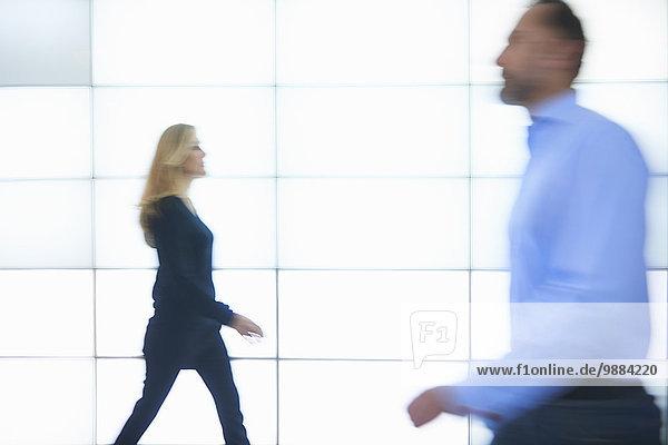 Mann und Frau gehen an hinterleuchteten Wandpaneelen vorbei.
