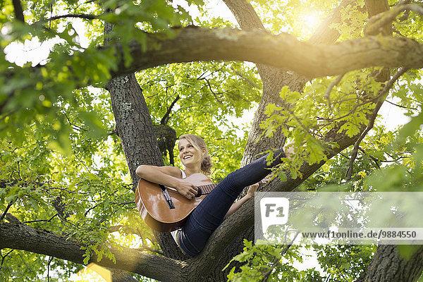 Tiefblick auf eine junge Frau  die auf einem Baumzweig sitzt und Akustikgitarre spielt.
