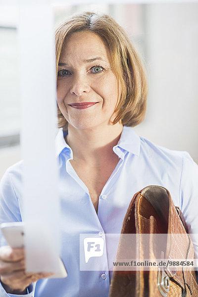 Reife Geschäftsfrau mit Smartphone und Aktentasche im Büro