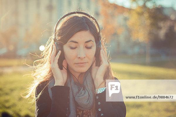Mittlere erwachsene Frau mit geschlossenen Augen  die Kopfhörer im Park hört.