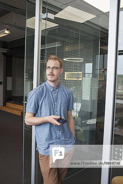 Junger Mann  der von der Bürotür blickt