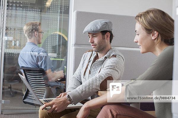 Mann und Frau betrachten Laptop in Bürobesprechung