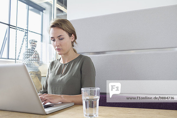 Junge Frau beim Tippen am Laptop im Büro Junge Frau beim Tippen am Laptop im Büro
