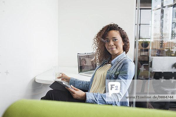 Porträt einer jungen Frau mit digitalem Tablett am Schreibtisch