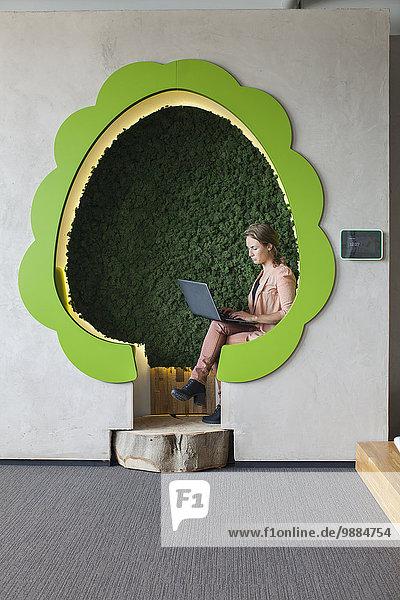 Designer bei der Arbeit am Laptop in baumförmigen Büroräumen Designer bei der Arbeit am Laptop in baumförmigen Büroräumen