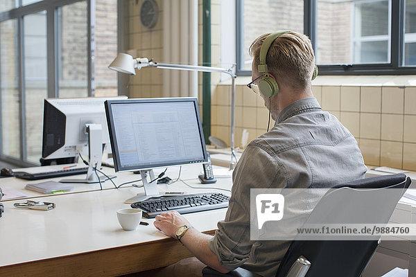 Rückansicht des Mannes  der während der Arbeit am Schreibtisch Kopfhörer hört.