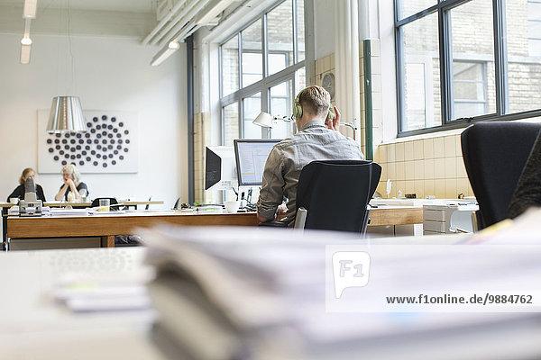 Rückansicht des Mannes  der am Schreibtisch arbeitet  während er Kopfhörer hört.