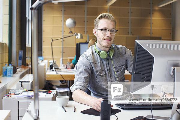 Porträt eines jungen Mannes mit Computer am Schreibtisch