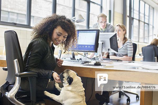 Junge Frau Streichelhund am Schreibtisch