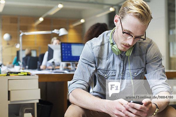 Junger Mann entscheidet sich für Musik vom Smartphone im Büro