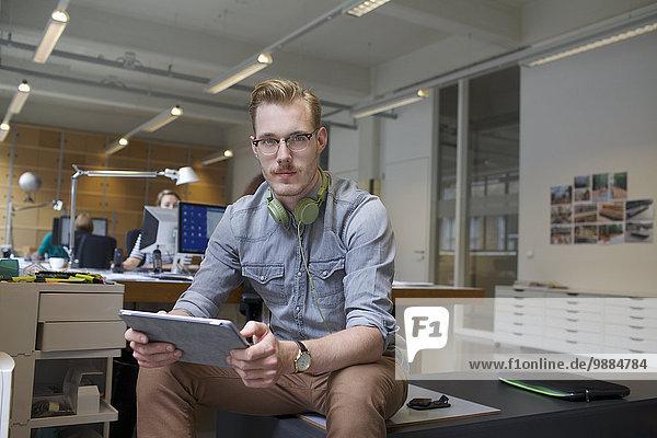 Porträt eines jungen Mannes mit digitalem Tablett im Büro