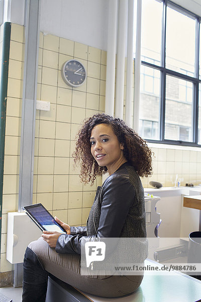 Porträt einer jungen Frau mit digitalem Tablett im Büro
