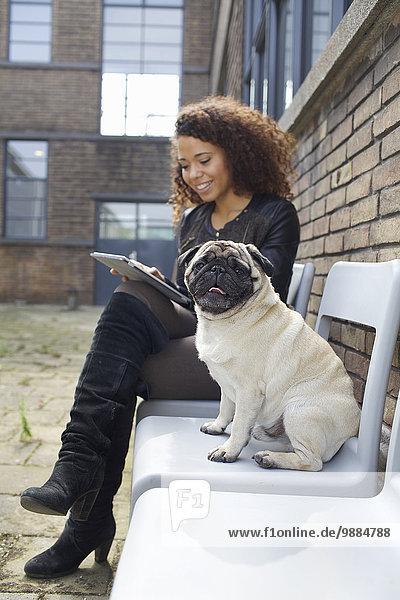 Porträt eines Mops auf Stuhl sitzend mit junger Frau im Bürohof