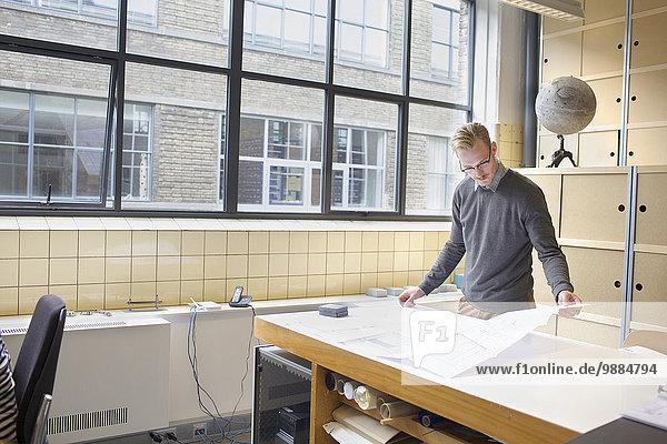 Männlicher Designer beim Betrachten des Entwurfs im Kreativbüro