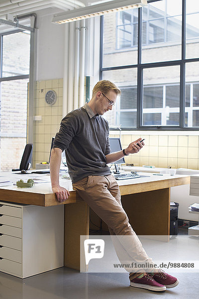 Männliche Designer suchen Smartphone im Kreativbüro