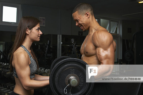 Young woman and mid adult man  lifting weights