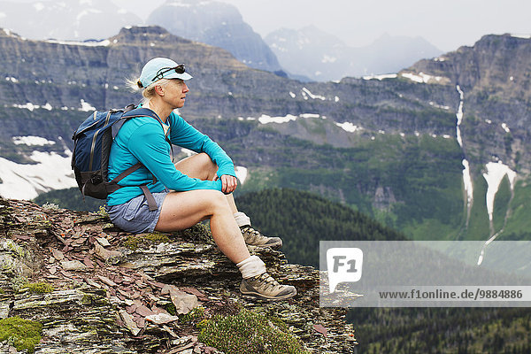 Female hiker sitting on a rock cliff overlooking the valley with a mountain range in the distance; Waterton  Alberta  Canada