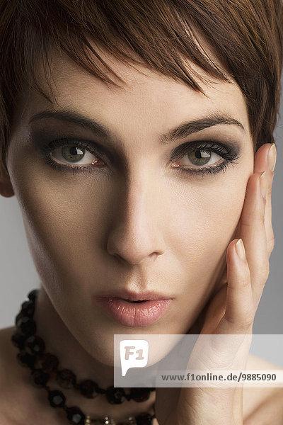 Nahaufnahme Studio-Porträt einer schönen Frau mit Hand auf der Wange
