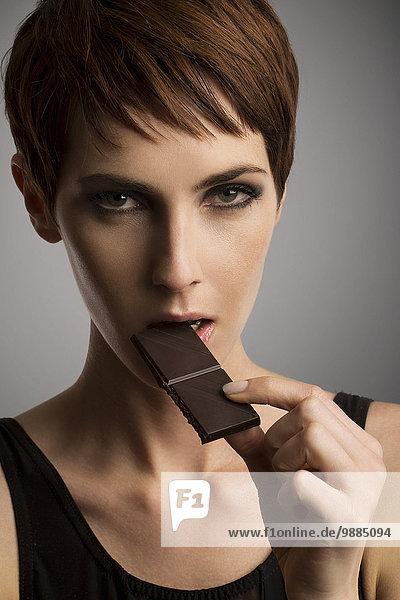 Studio-Porträt einer Frau beim Essen von dunkler Schokolade