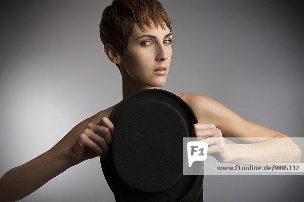 Studio-Porträt einer Frau mit Zylinder vor der Brust