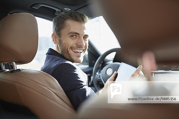 Portrait of young businessman using digital tablet in car